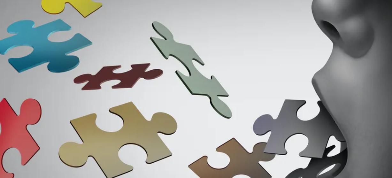 Imagen de una boca lanzando piezas de puzle