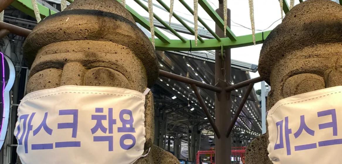 Dos esculturas de piedra con mascarillas con la leyenda Use mascarilla en Jeju, Corea del Sur