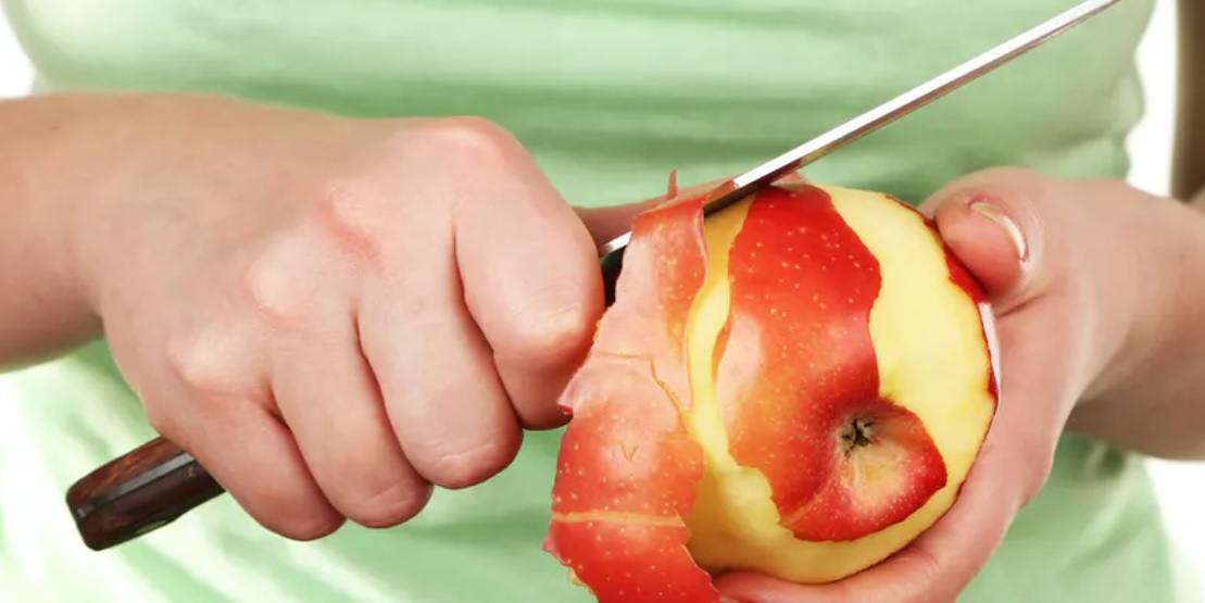 Mano pelando una manzana