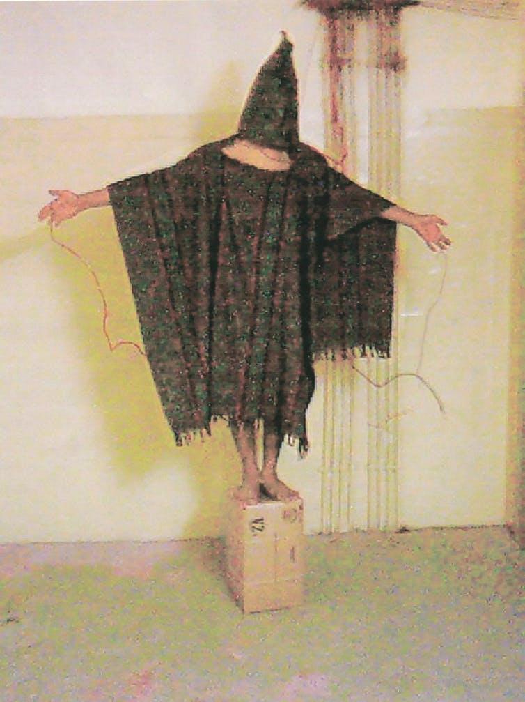 El prisionero de la prisión de Abu Ghraib (Irak) Abdou Hussain Saad Faleh (Gilligan), siendo torturado con cables electrificados conectados a sus manos y genitales. Fotografía tomada el 4 de noviembre de 2003