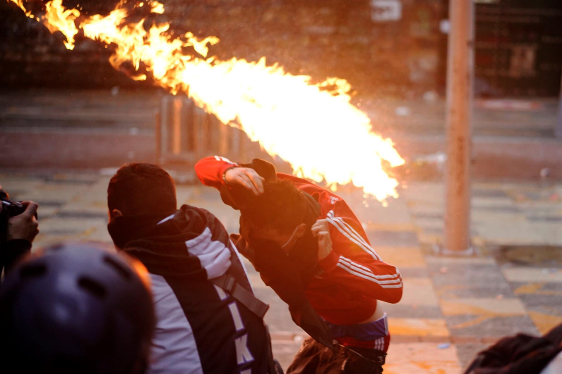 Un hombre se cubre del fuego durante un enfrentamiento con la Policía en el centro de Bogotá (Colombia).- EFE