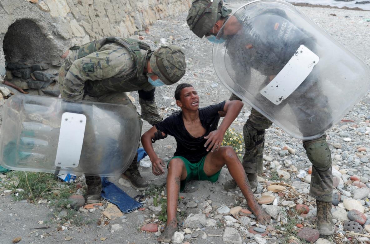 Un niño marroquí llora frente a soldados españoles después de nadar usando botellas como flotador, en la playa El Tarajal, para cruzar la frontera. - Jon Nazca / REUTERS