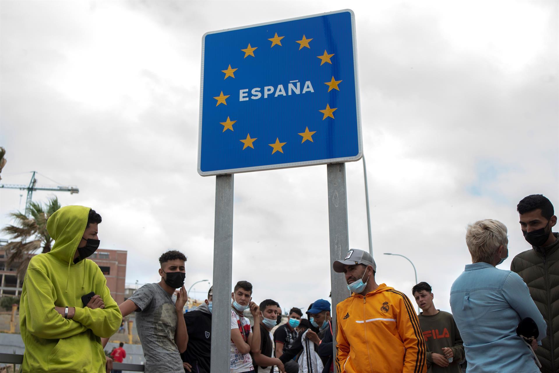 Varios migrantes esperan para pasar la frontera entre Ceuta y Marruecos voluntariamente. - EFE