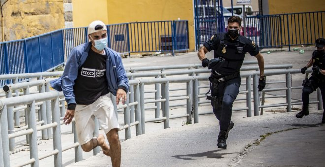 Un joven migrante intenta escapar de las naves del Tarajal en Ceuta mientras es perseguido por dos policías. -Jairo Vargas / ARCHIVO