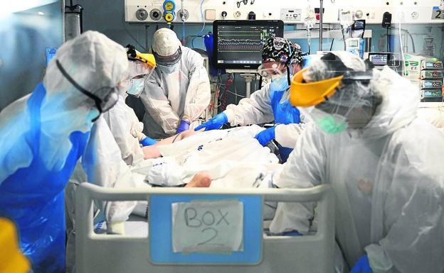 Sanitarios atienden a un paciente de Covid-19 en la UCI de un hospital barcelonés. / EFE