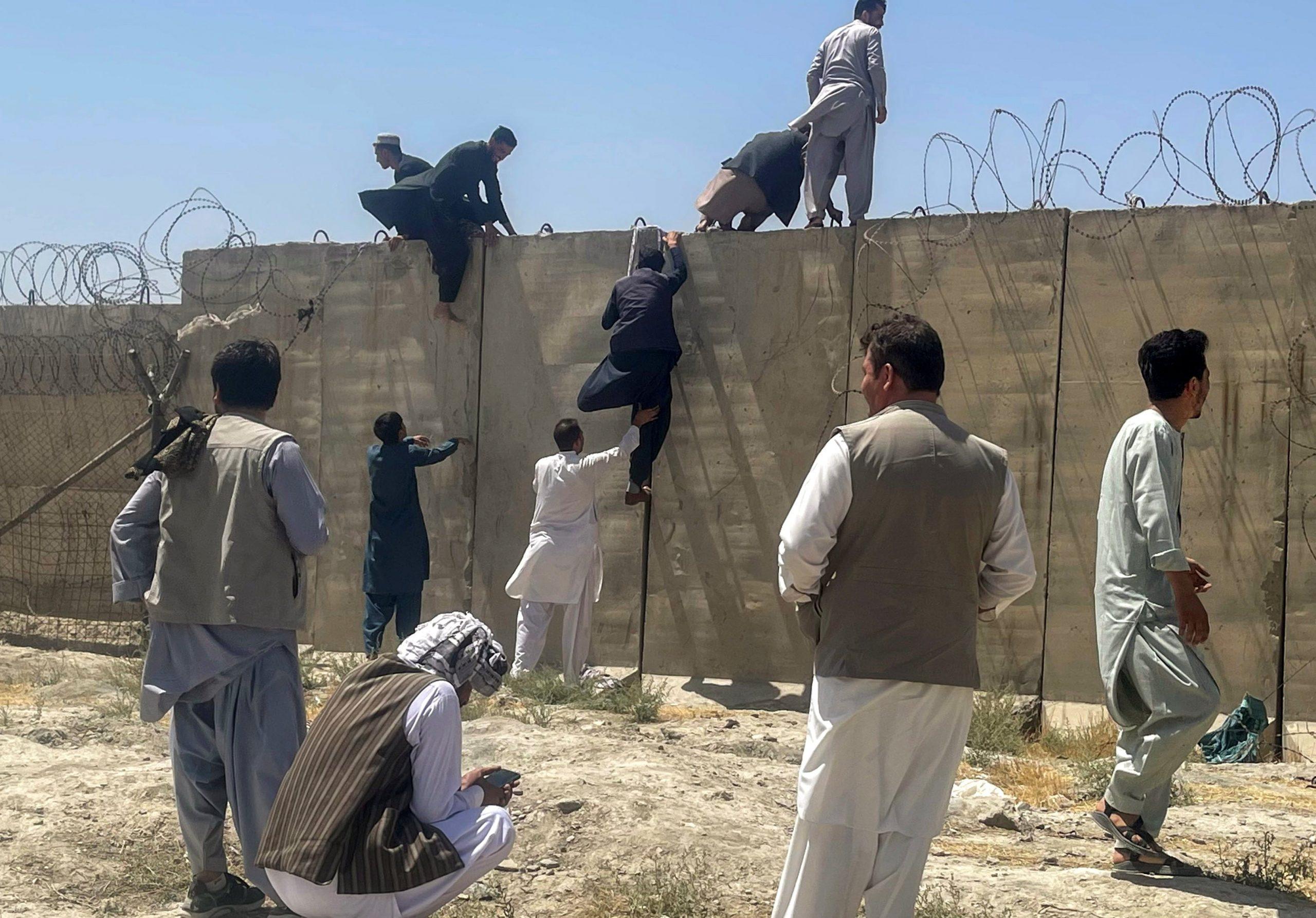 Hombres afganos tratan de entrar en el Aeropuerto de Kabul tras la victoria talibán. REUTERS