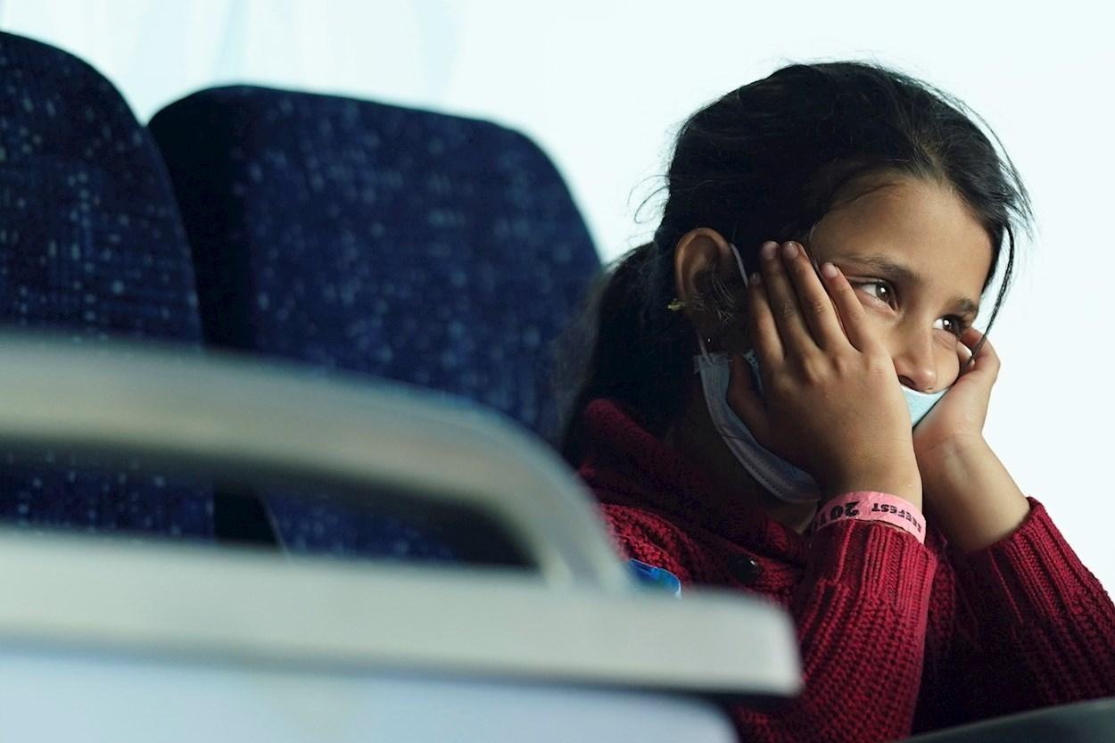 Una niña afgana, integrante de un grupo de ciudadanos evacuados de Kabul, permanece en un autobús tras su llegada al aeropuerto internacional Washington Dulles. EFE/ Will Oliver