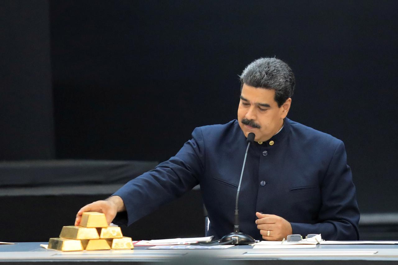 Nicolás Maduro toca unos lingotes de oro, en una reunión con ministros del área económica, en el Palacio de Miraflores (Caracas), en marzo de 2018. REUTERS/Marco Bello