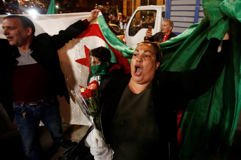 Una mujer con una bandera de Argelia celebra el anuncio de dimisión del presidente Abdelaziz Bouteflika. /REUTERS