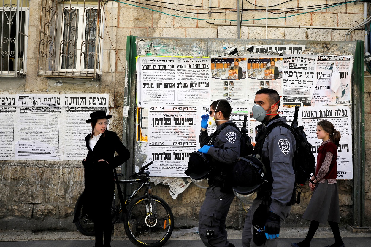 Policías israelíes con mascarillas patrullan por el bario de judios ultra-ortodoxos de Mea Shearim, en la zona norte de Jerusalén. REUTERS/Ronen Zvulun