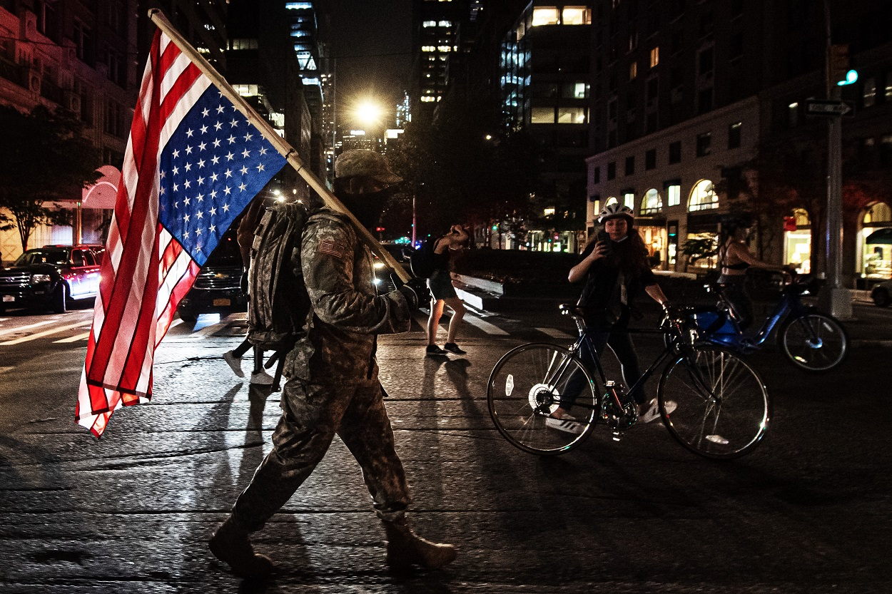 Un manifestante viste ropa militar y lleva la bandera de EEUU durante una protesta en Manhattan contra la muerte violenta del afroamericano George Floyd por un policía blanco en Minneapolis. E.P./Joel Marklund/ZUMA Press/dpa