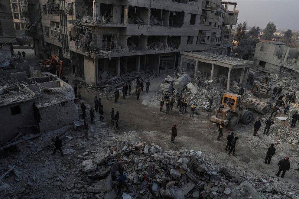 Foto de archivo (09/01/2018) de civiles y voluntarios de la Defensa Civil Siria mientras buscan supervivientes después de que varios ataques aéreos en Hamoria, al-Ghouta (Siria). — MOHAMMED BADRA / EFE