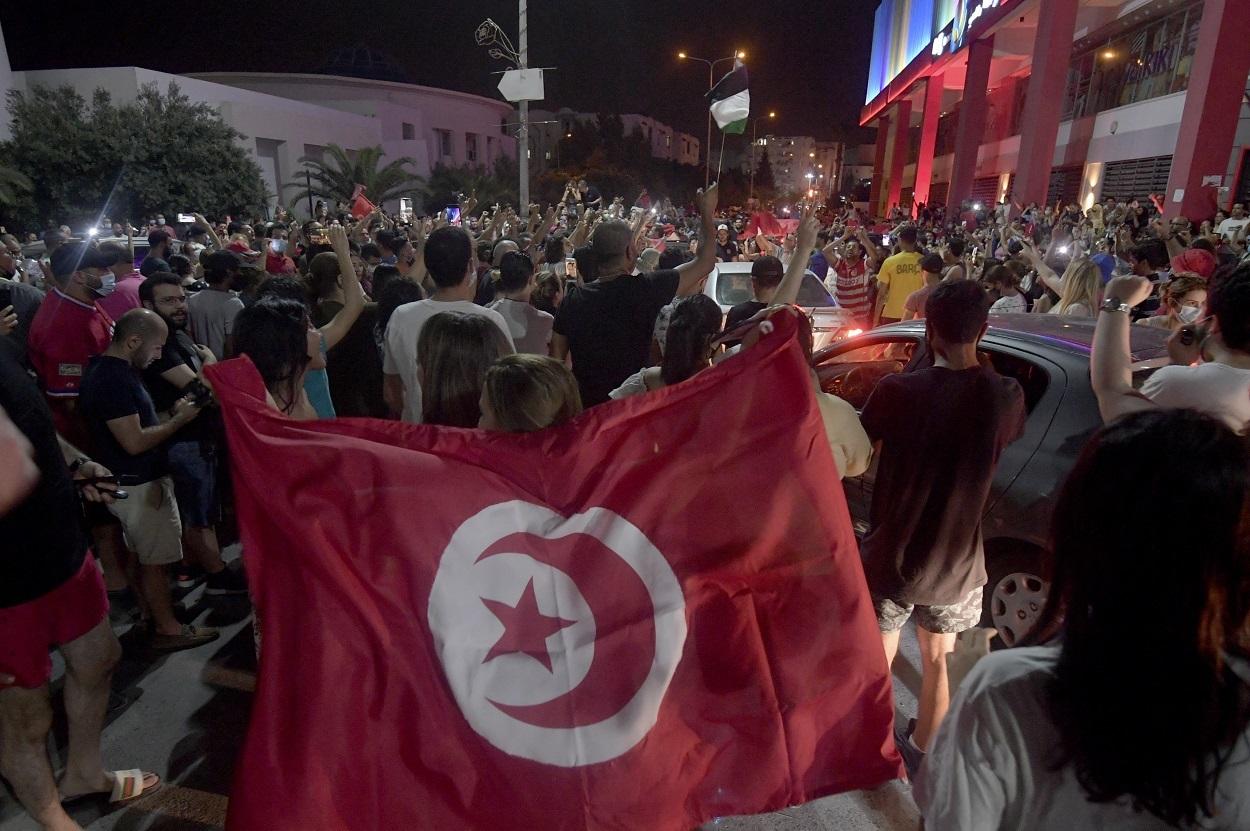La gente celebra en las calles de Túnez después de que el presidente tunecino Kais Saied anunciara la suspensión del Parlamento y la destitución del primer ministro Hichem Mechichi, tras las protestas contra el partido gobernante. AFP/FETHI BELAID