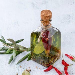Aceite picante con guindillas y plantas aromáticas.