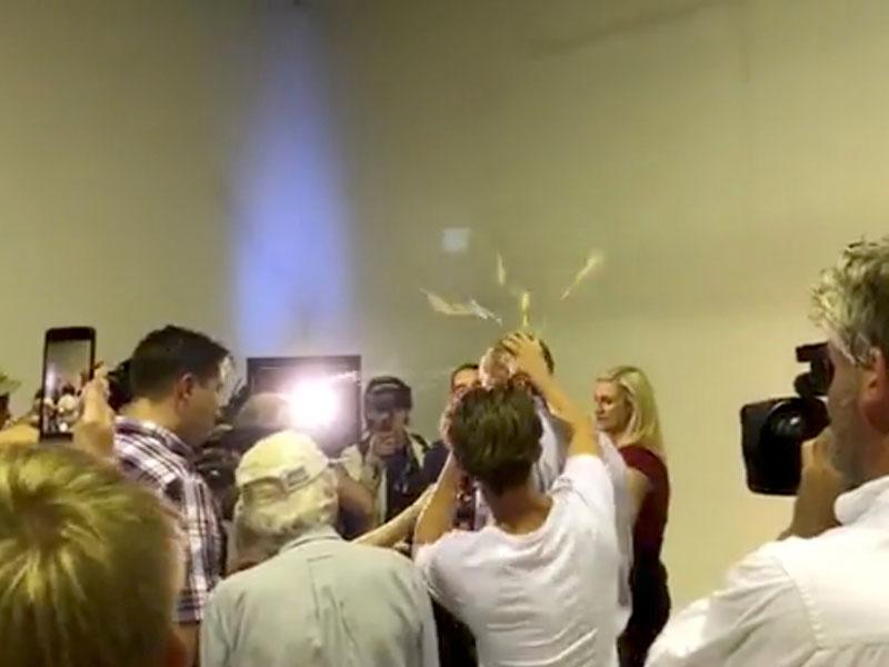 Momento en el que un joven estrella un huevo en la cabeza del senador australiano Fraser Anning mientras hablaba con los periodistas. REUTERS