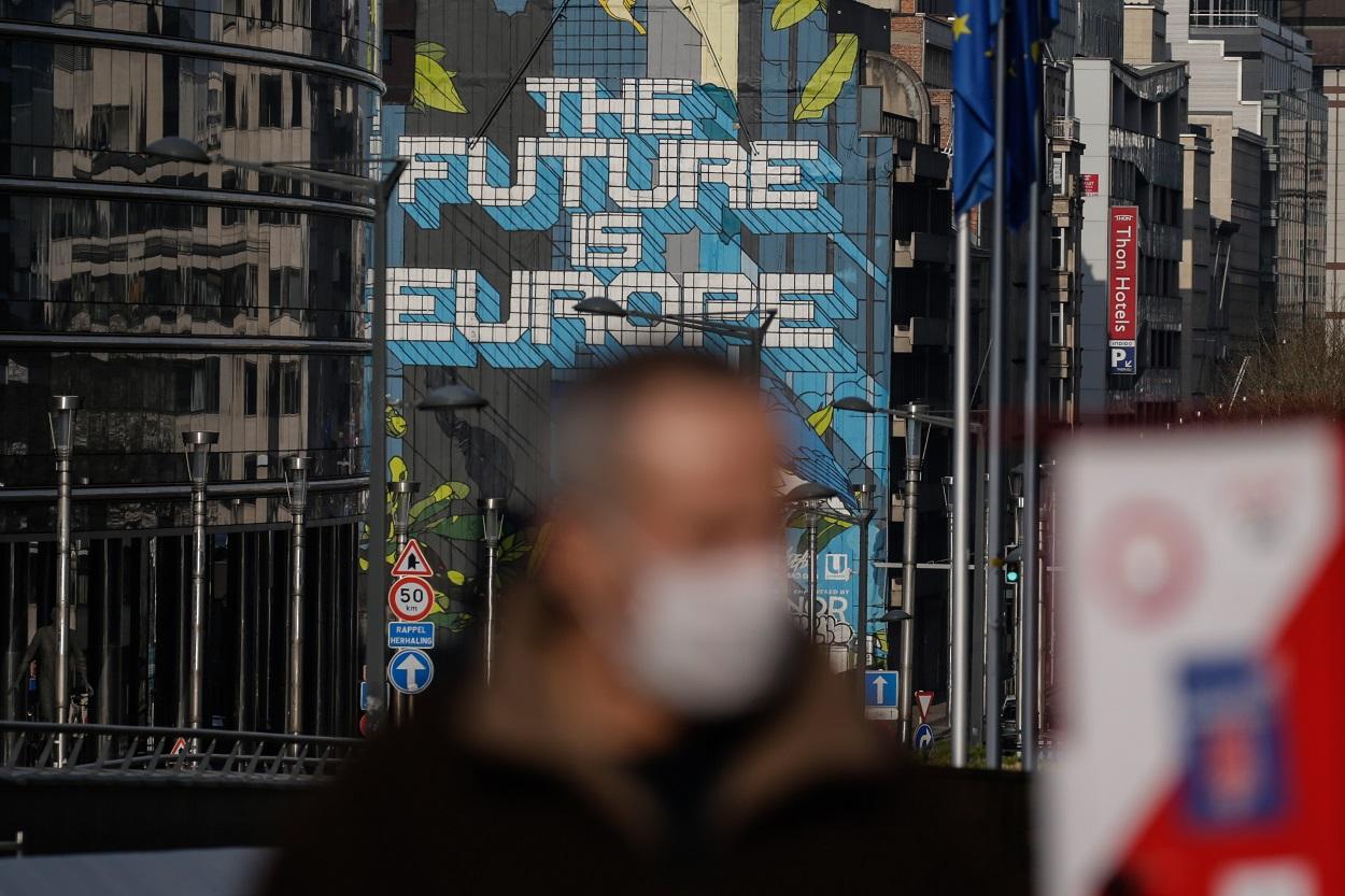 Un hombre con mascarilla pasa por delante del edificio de la Comisión Europea, en Bruselas. AFP/Aris Oikonomou