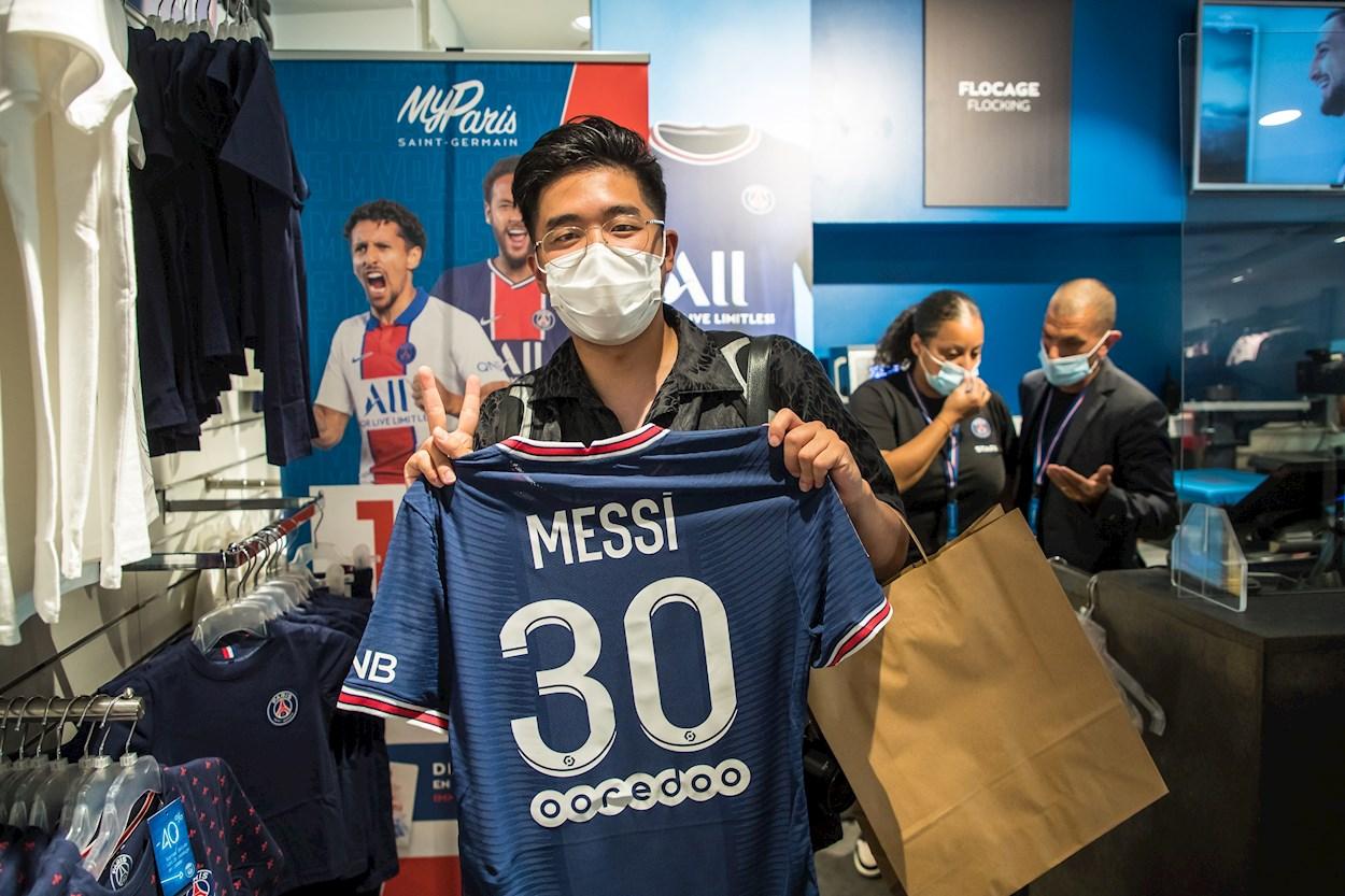 Un aficionado hace el signo de la victoria mientras sostiene la camiseta con el nombre y el número de Lionel Messi en el Paris Saint Germain, en la tienda oficial del equipo en los Campos Elíseos de París. EFE/CHRISTOPHE PETIT TESSON