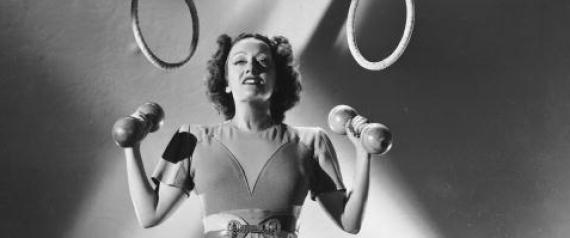 circa 1930: American actress Gloria Swanson (1899 - 1983) lifts a pair of small weights while a set of rings hang over her head. (Photo by Ernest Bachrach/John Kobal Foundation/Getty Images)