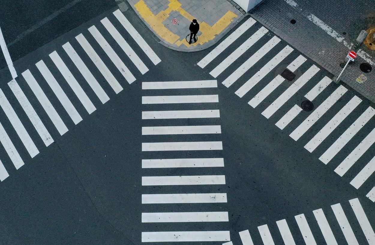 Un hombre con mascarilla parado en el conocido cruce de calles de Tokio frente a la estación de Shinjuku, prácticamente desértico por las medidas de emergencia decretadas por el gobierno japonés frente a la pandemia del coronavirus. REUTERS/Kim Kyung-Hoon