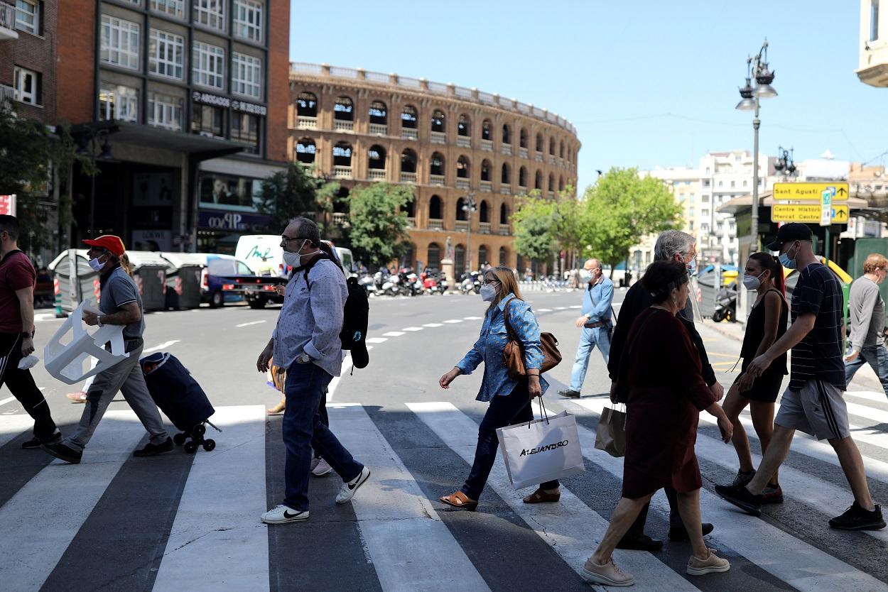 Varias personas, muchas con mascarilla, cruzan la calle cerca de la Plaza de Toros de Valencia. REUTERS/Nacho Doce
