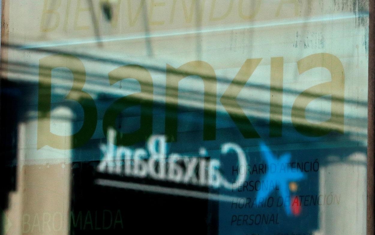 El logo de una oficina de Caixabank se refleja en la ventana de una sucursal de Bankia, en Barcelona. REUTERS/Albert Gea
