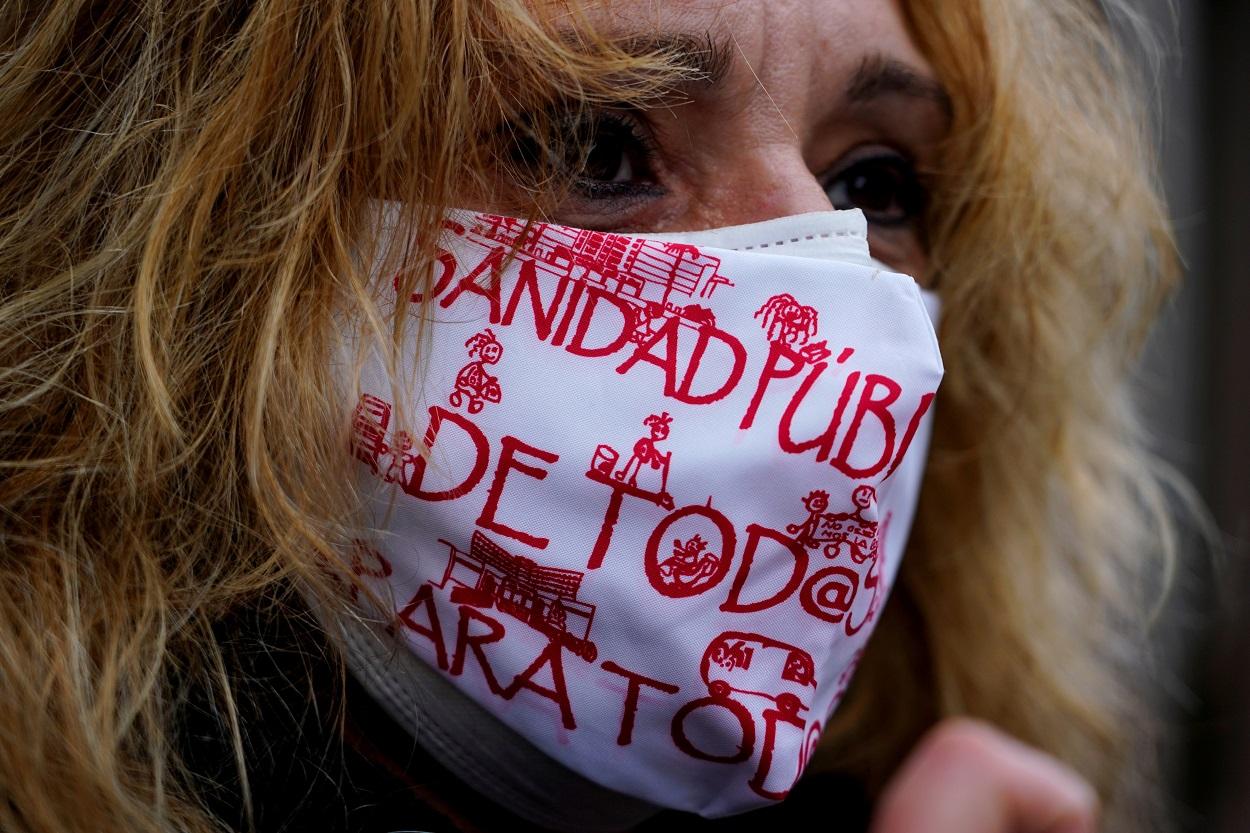 Una mujer con mascarilla, con lemas a favor de la sanidad pública, en una manifestación en Madrid. REUTERS/Juan Medina